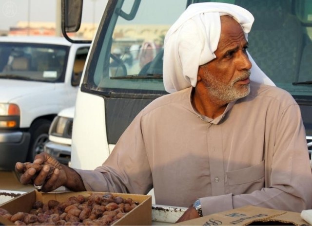 Saudi man inspects dates during the Ahsa Festival for Palms and Dates in the Eastern Province SPA
